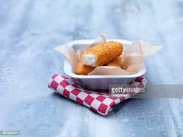 Fried chunky breaded cod fish fingers in baking tin on steel table