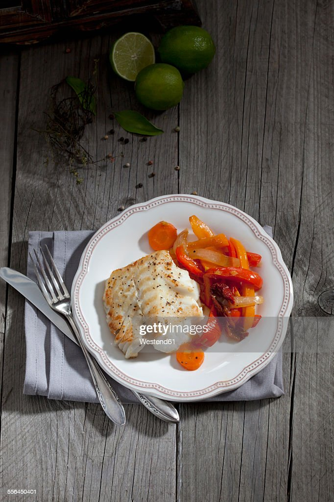 Fried codfisch and vegetables on plate