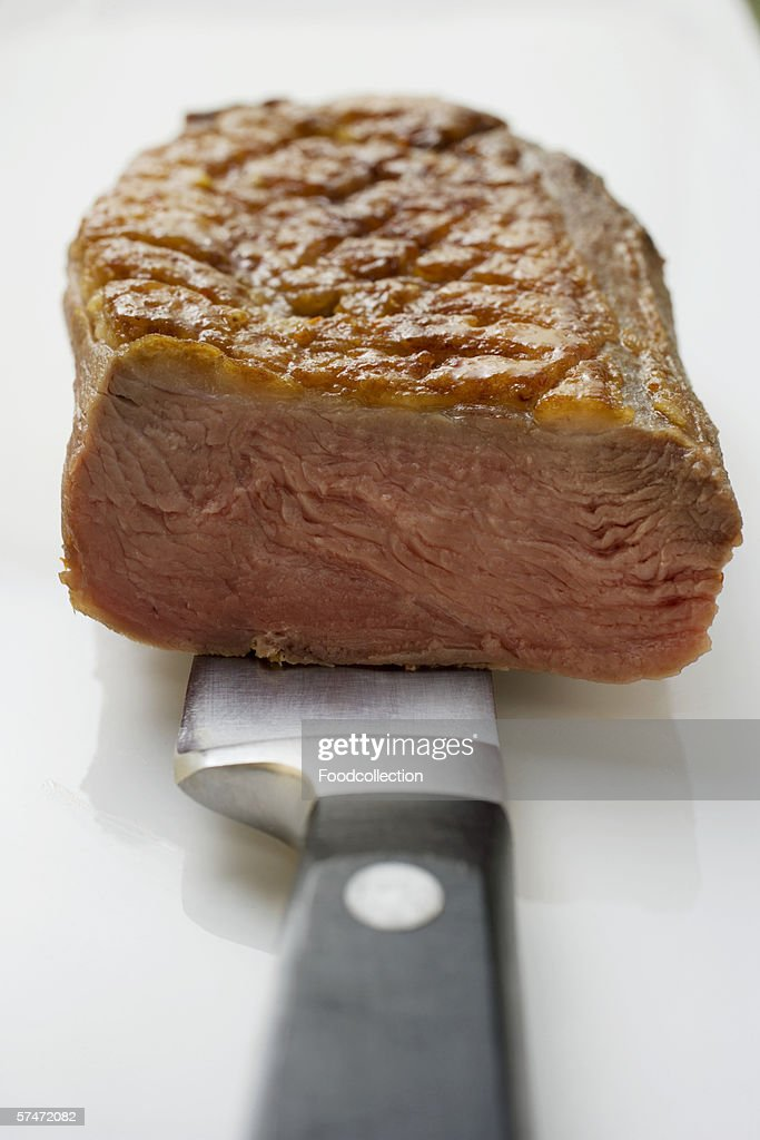 Fried duck breast, a piece cut off, on knife : Stock Photo