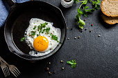 Fried egg. Close up view of the fried egg on a frying pan. Salted and spiced fried egg with parsley on cast iron pan and black background.