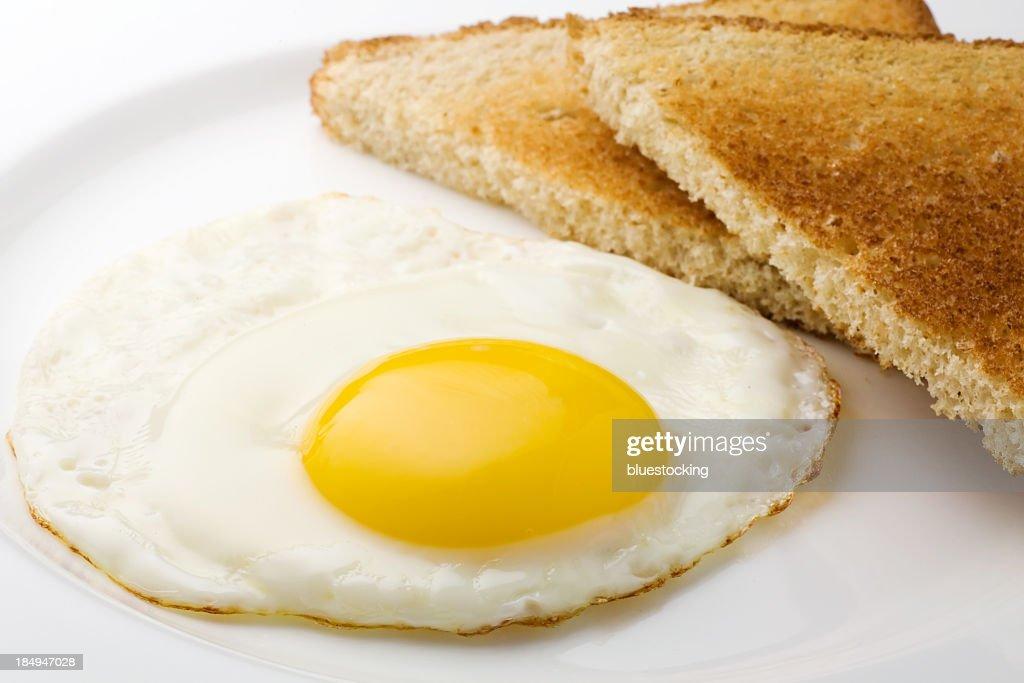 Fried egg sunny side up and plain sliced toast