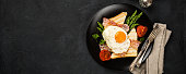 Breakfast or lunch with Fried egg, bread toast, green asparagus, tomatoes and bacon on black plate. Top view. Copy space. Banner.
