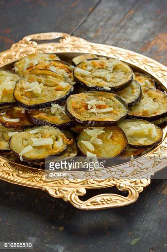 fried eggplant with garlic in vintage golden dish : Stock Photo