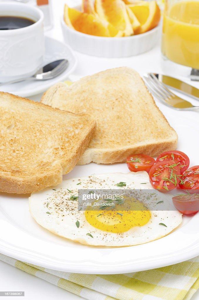 Uova fritte, pomodori freschi e croccanti brindisi per la prima colazione : Foto stock