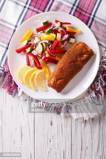 fried fish fillet with fresh vegetables and a lemon. vertical : Stock Photo