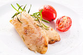 Fried fish fillet with tomatoes as closeup on a white plate