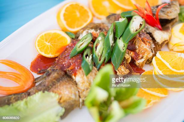 fried fish with fresh herbs and orange fruits