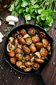 Cooked fried mushrooms in pan on wooden table, top view