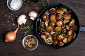 Delicious fried mushrooms in frying pan on wooden table, top view