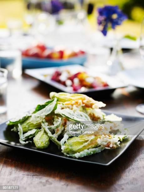 Fried organic squash blossoms on platter