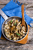 Fried oyster mushrooms with onions and spices in a plate on a wooden background. Selective focus.