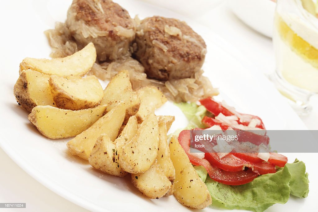 Fried potato wedges with meatball and vegetable salad : Stock Photo
