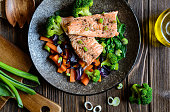 Fried salmon steaks with steamed carrot, broccoli, onion and spinach