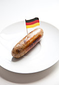 Fried sausage in plate with German flag decoration against white background
