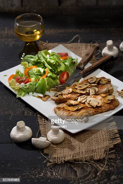Fried schnitzel with mushrooms and salad on plate
