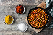 Fried spicy chickpeas in frying pan on wooden background