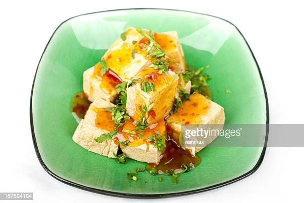 Fried squares of tofu served on green ceramic plate