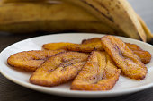 Freshly fried sweet plantains served on a white plate.  Green plantains will ripen in a few days.  When the plantain changes color from green to yellow and it becomes softer to the touch with a few sp