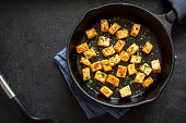 Fried tofu with sesame seeds and spices on cast iron pan, copy space. Healthy ingredient for cooking vegan vegetarian diet food. Roasted tofu over black background.