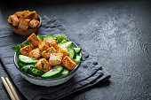 Fried Tofu Salad with Cucumbers and Sesame Seeds. Homemade asian vegetable and tofu salad in ceramic bowl on black stone background. Healthy asian diet vegan vegetarian salad food.