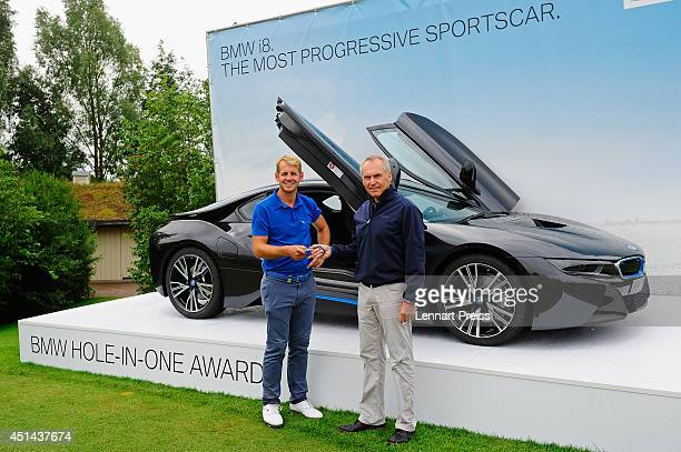Friedrich Eichiner CFO of BMW Group hands over the key of a BMW i8 car to James Heath of England winner of the Hole in One Contest at hole 16 of the...