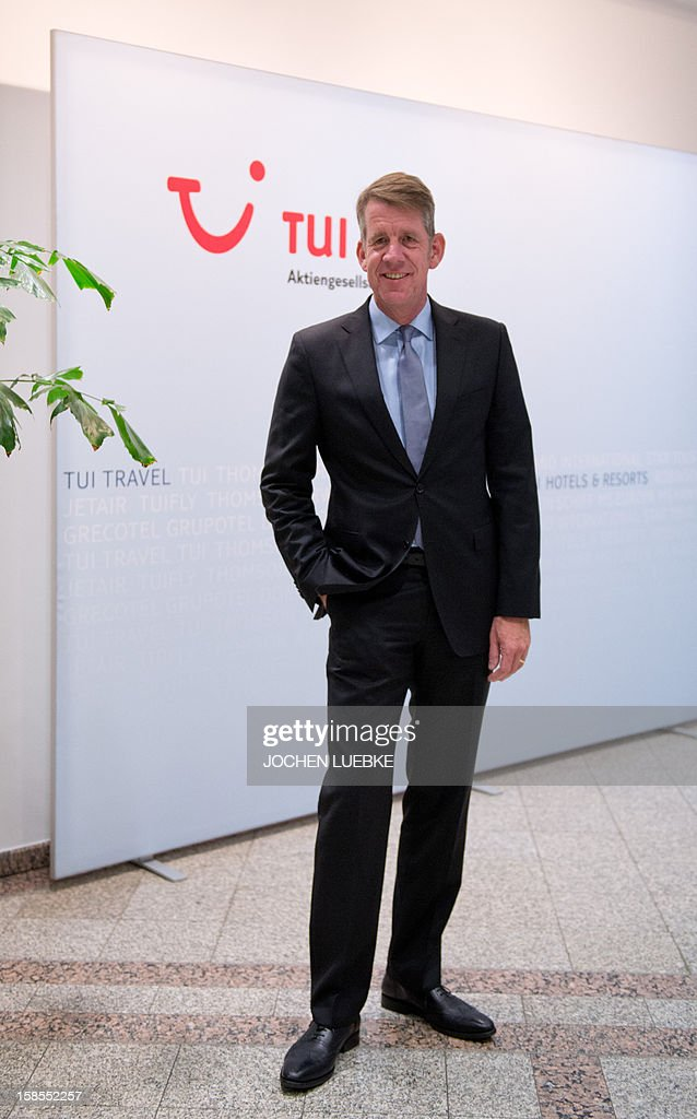 Friedrich Joussen, designated chairman of German tourism giant TUI, poses in front of his company's logo on the sidelines of a press conference in Hanover, central Germany, on December 19, 2012. TUI posted a net loss for the 2012 financial year due to difficulties at shipping company Hapag Lloyd in which it holds a stake. AFP PHOTO / JOCHEN LUEBKE GERMANY OUT