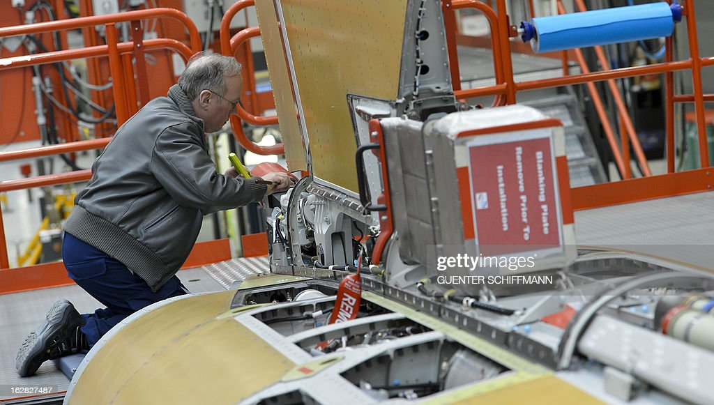 Friedrich Wittmann, employee of the EADS company Cassidian, controls with a mirror the cabling during the assembling of an Eurofighter plane for the German Air Force at the Cassidian production line in Manching, southern Germany, on February 28, 2013.