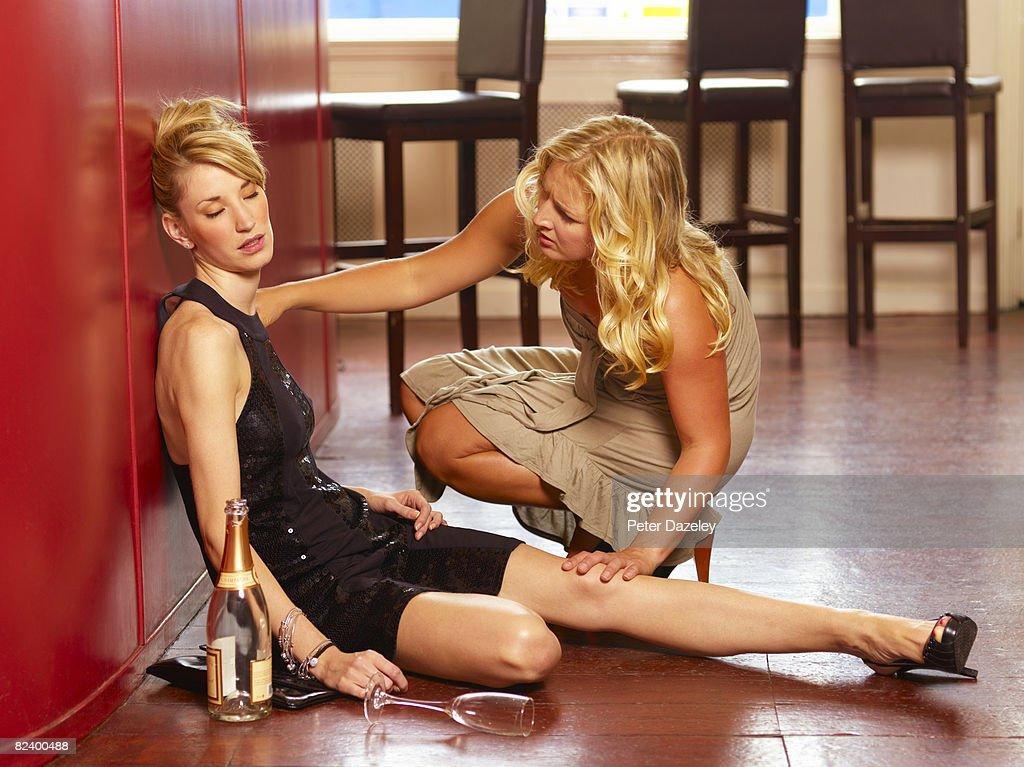 Friend helping unconscious drunk