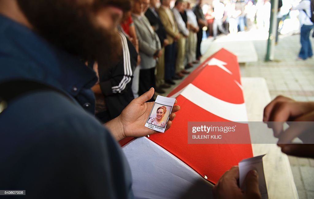 A friend of air hostess Gulsen Bahadir killed during last night attacks, holds a picture of her next to the coffin during the funeral in Istanbul, on June 29, 2016, a day after a suicide bombing and gun attack targeted Istanbul's airport, killing at least 36 people. A triple suicide bombing and gun attack that occurred on June 28, 2016 at Istanbul's Ataturk airport has killed at least 36 people, including foreigners, with Turkey's prime minister saying early signs pointed to an assault by the Islamic State group. / AFP / BULENT