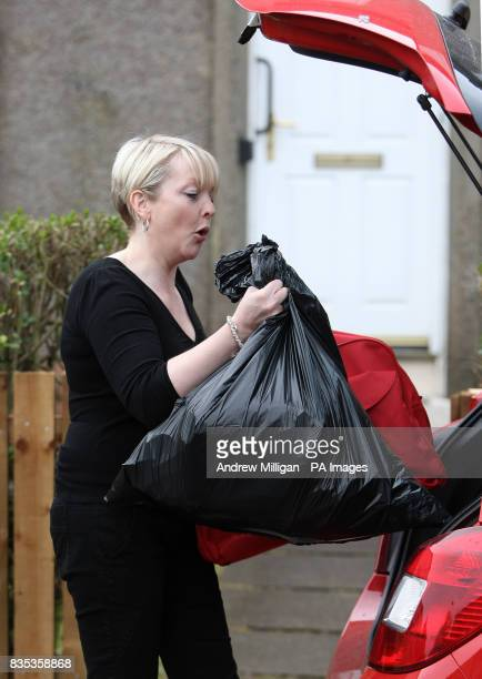 A friend of Britain's Got Talent star Susan Boyle loads her car with bags outside her home in Blackburn West Lothian