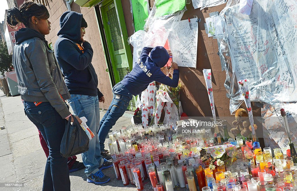 A friend of Kimani Gray signs a poster at a memorial for the 16-year-old boy March 15, 2013 in New York. Kimani Gray was shot by two police officers late on Saturday in Brooklyn's East Flatbush neighborhood after police said he pointed a handgun at them. Gray's family has denied the teen was armed. An autopsy revealed that Gray had been shot seven times, including three times in the back. Although the report did not detail the order in which the bullets struck Gray, the revelations increased tensions among the already furious community. AFP PHOTO/DON EMMERT