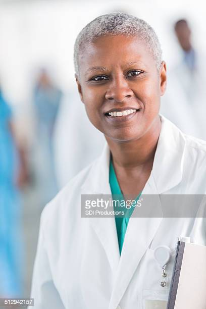 Friendly African American female doctor smiling in busy hospital