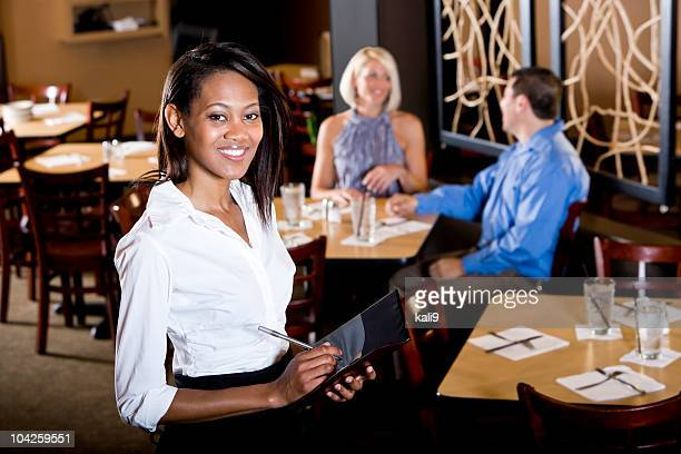 Friendly African-American waitress in restaurant taking customer orders