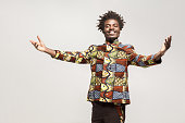 Friendly afro man in traditional clothes toothy smile, say welcome. Indoor, isolated on gray background