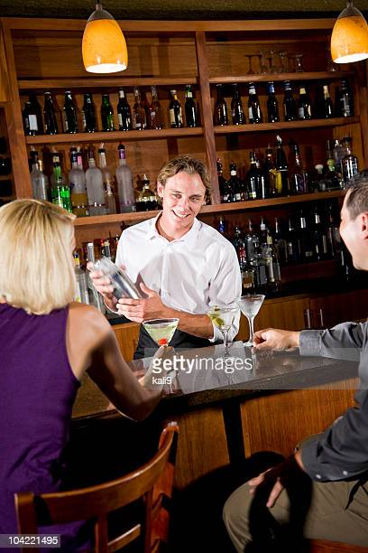 Friendly bartender mixing drink chatting with couple in restaurant bar