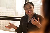 Friendly black businesswoman leader discussing work with colleague at the meeting in office