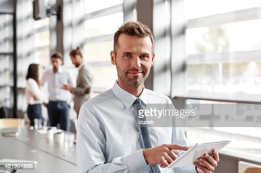Friendly businessman using a digital tablet in the office