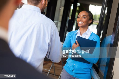 Friendly businesswoman shaking hands and greeting client in office doorway