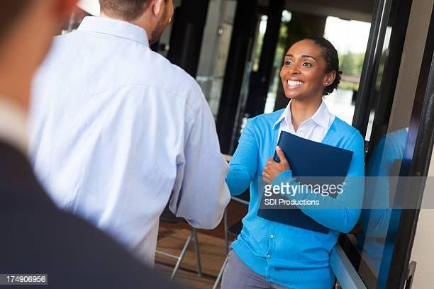 Sympathique Femme d'affaires se serrent la main et se saluer le client au bureau de porte