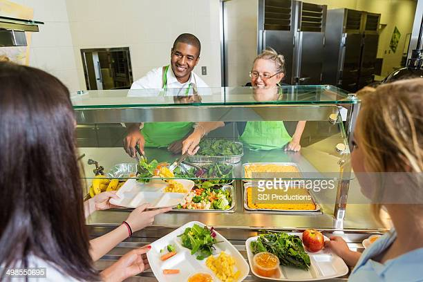 Friendly cafeteria workers serving healthy food to high school students