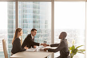 Friendly caucasian employers and confident african-american applicant handshaking during job interview sitting at office desk with big large window urban buildings cityscape at background, side view