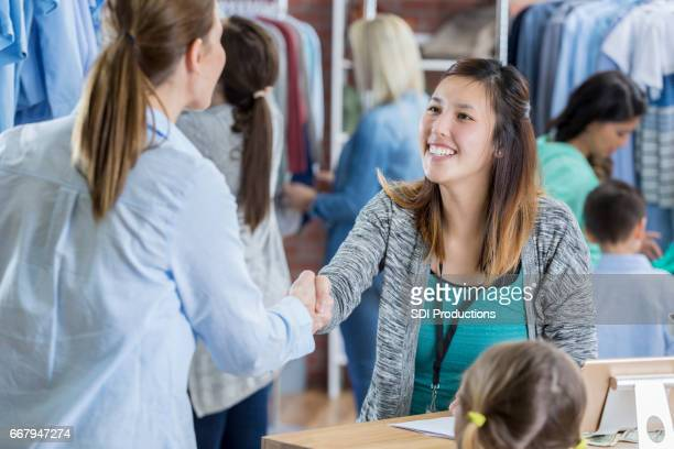 Friendly clothing store employee greets customer