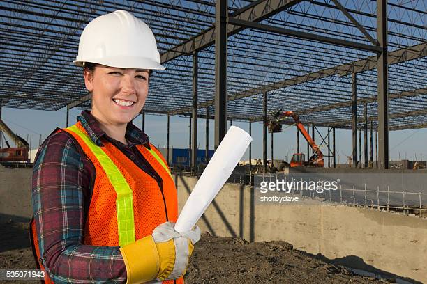 Friendly Female Construction Architect and Blueprints at a Building Site