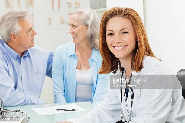 Friendly female doctor consulting with senior couple patients