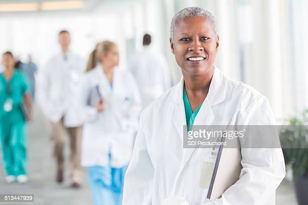 Friendly female doctor smiling in crowded hospital