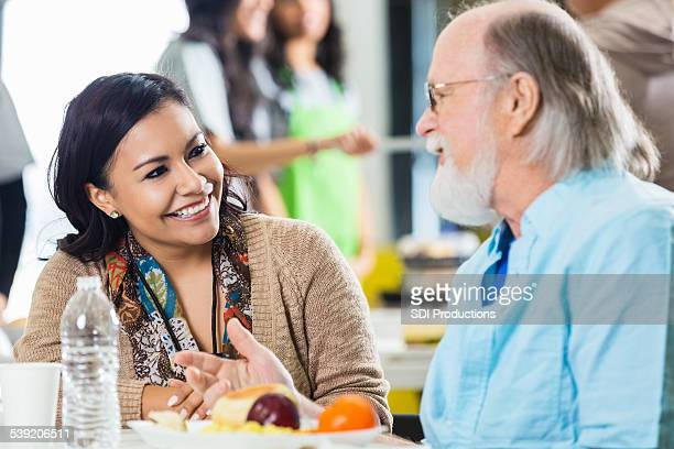 Friendly food bank volunteer taking to senior man during meal