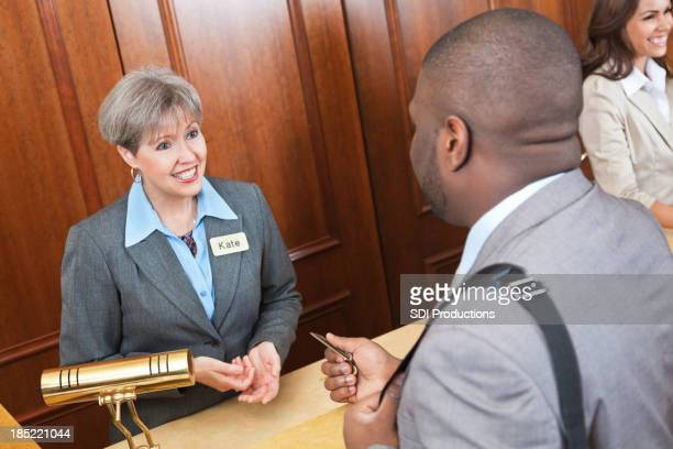Friendly front desk lady helping hotel guest