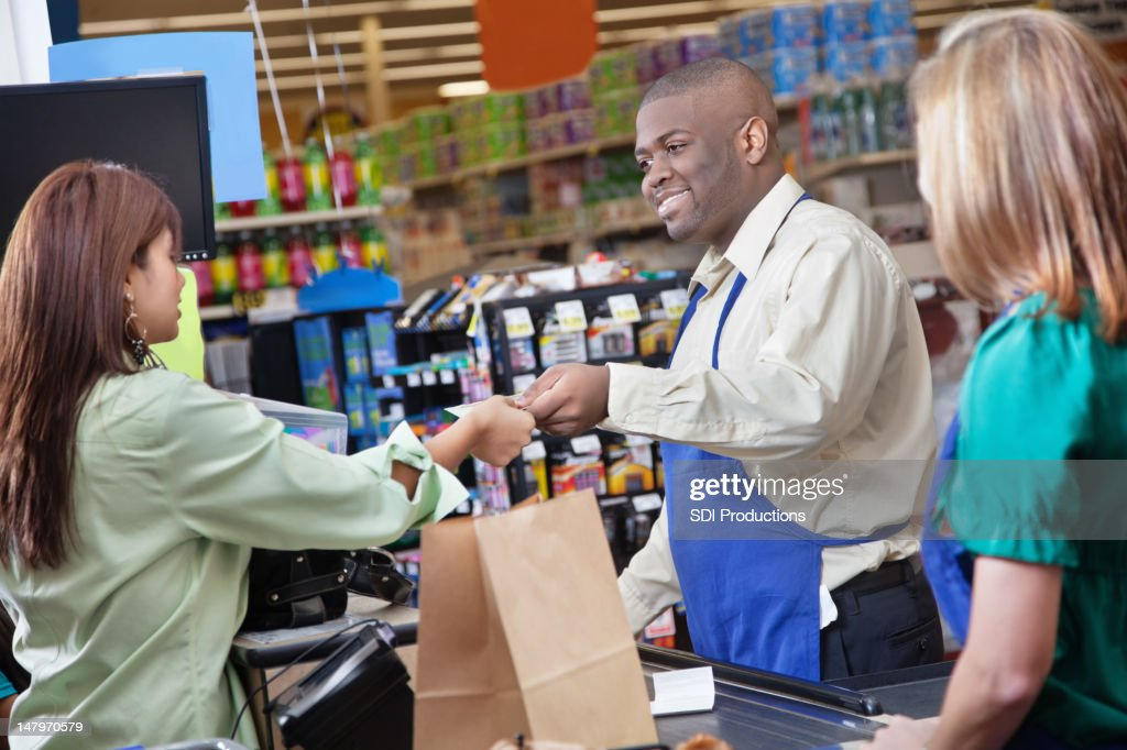 Friendly grocery store clerk giving change to customer : Stock Photo