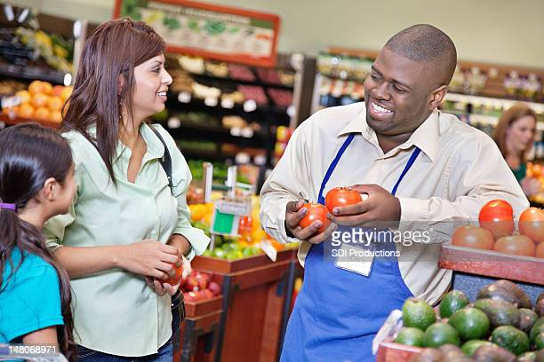 Friendly grocery store worker helping customers in supermarket