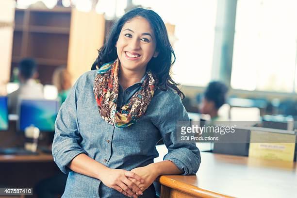 Friendly Hispânico mulher de pé no balcão da biblioteca, consulte